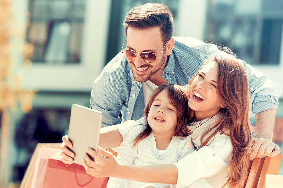 Client Center - Happy Family Sitting On Bench Outside In City Using Tablet